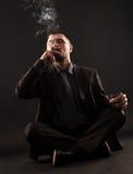 Geschäftsmann, der im Lotussitz, meditateing sitzt Lizenzfreie Stockbilder