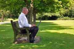 Geschäftsmann, der im Park arbeitet Lizenzfreie Stockfotografie