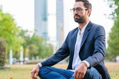 Geschäftsmann, der im Park meditiert stockfoto