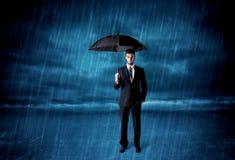Geschäftsmann, der im Regen mit einem Regenschirm steht Stockfoto