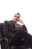 Geschäftsmann, der im schwarzen Bürostuhl sitzt Stockbild