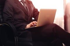 Geschäftsmann, der im Stuhl sitzt und an Computer in seinem Büro während Sonnenuntergangglanz zum Fenster arbeitet Warmes Tonen Stockfotografie