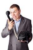 Geschäftsmann, der im Telefonempfänger schreit Lizenzfreie Stockfotografie