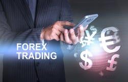 Geschäftsmann, der intelligente Telefonwelt des Währungsdevisenhandels hält Stockfotografie