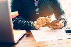 Geschäftsmann, der intelligentes Telefon hält und mit Laptop arbeitet Lizenzfreies Stockbild