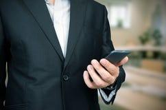 Geschäftsmann, der intelligentes Telefon im Büro verwendet Stockfotografie