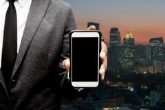 Geschäftsmann, der intelligentes Telefon mit Stadtlichthintergrund hält Stockbild