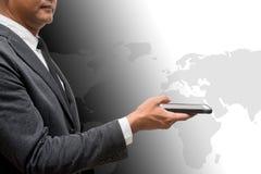 Geschäftsmann, der intelligentes Telefon mit Weltkarte im Hintergrund hält Stockfoto