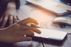 Geschäftsmann, der intelligentes Telefon und Arbeit mit Laptop auf dem tabl hält Lizenzfreie Stockfotografie