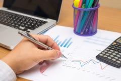 Geschäftsmann, der Investitionsdiagramme mit Laptop analysiert Stockbilder