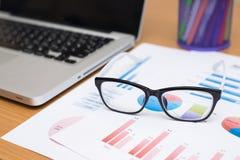 Geschäftsmann, der Investitionsdiagramme mit Laptop und Gläsern analysiert Lizenzfreies Stockbild