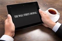 Geschäftsmann, der ipad mit Wall Street Journal auf dem Schirm hält Stockbild