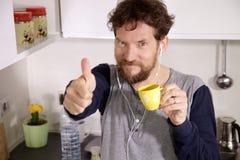 Geschäftsmann in der Küche, die okayzeichensieger des Kaffees hält lizenzfreie stockbilder