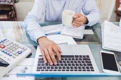 Geschäftsmann, der Kaffeetasse während zu Hause arbeiten hält Lizenzfreies Stockfoto