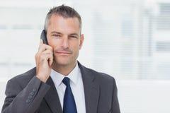 Geschäftsmann, der Kamera beim Haben eines Telefonanrufs betrachtet Stockbilder