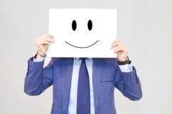 Geschäftsmann, der Karte mit glücklichem Gesicht auf grauem Hintergrund hält Stockfoto