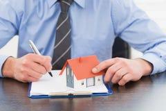 Geschäftsmann, der Kenntnisse nimmt und Miniaturhaus hält Lizenzfreies Stockfoto