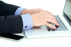 Geschäftsmann, der Kenntnisse von einem Laptop nimmt Stockfotografie