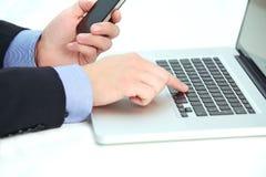 Geschäftsmann, der Kenntnisse von einem Laptop nimmt Lizenzfreie Stockbilder