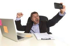 Geschäftsmann in der Klage, die am Bürolaptopcomputertisch unter Verwendung des Handys für das Machen von selfie Foto arbeitet Stockbild