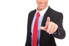Geschäftsmann in der Klage, die eine Taste eindrückt Lizenzfreies Stockbild