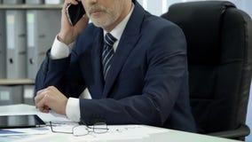 Geschäftsmann in der Klage, die im Büro arbeitet, mit Kunden über Telefon wählt und spricht stock video footage
