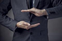 Geschäftsmann in der Klage mit zwei Händen in der Position, zum etwas zu schützen Lizenzfreie Stockfotos