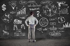 Geschäftsmann in der Klage und im Unternehmensplan Stockbild