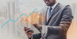 Geschäftsmann in der Klagenholding-Tablettenstellung über unscharfem Stadthintergrund und erfolgreichem Diagrammvordergrund stockfoto