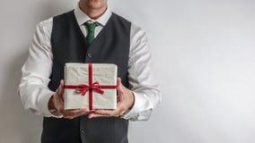 Geschäftsmann in der Klagenweste, die ein Weihnachtsgeschenk/-geschenk hält lizenzfreie stockfotos