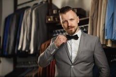 Geschäftsmann in der klassischen Weste gegen Reihe von Klagen im Shop Ein junger stilvoller Mann in einer schwarzen Stoffjacke Es Lizenzfreie Stockfotos