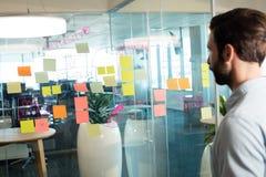 Geschäftsmann, der klebende Anmerkungen und Strategie auf Glas betrachtet Lizenzfreie Stockbilder
