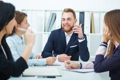 Geschäftsmann, der Kollegen bei einer Sitzung sich darstellt Stockbilder