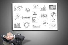 Geschäftsmann, der Konzept der grafischen Analyse betrachtet Stockfotos