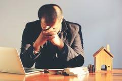 Geschäftsmann, der Kopfschmerzen, ermüdet und Belastung über Immobilien- und Besitzeigentum, glaubend betontes und Gesundheitswes stockfotos
