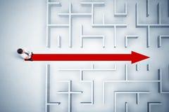 Geschäftsmann, der Labyrinth mit rotem Pfeil betrachtet Stockfotografie