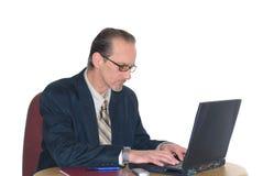 Geschäftsmann, der an Laptop arbeitet Stockbild