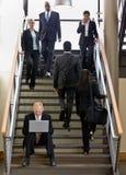 Geschäftsmann, der an Laptop auf Bürotreppen arbeitet Lizenzfreies Stockbild