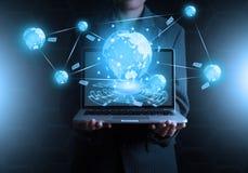 Geschäftsmann, der an Laptop-Computer über Weltkarte für soziales hält Lizenzfreies Stockfoto