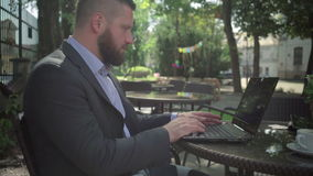 Geschäftsmann, der an Laptop, Neigungsschuß arbeitet outdoor stock footage