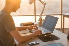 Geschäftsmann, der an Laptop am Schreibtisch im Büro arbeitet Stockfotos