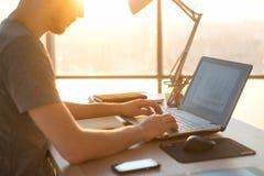 Geschäftsmann, der an Laptop am Schreibtisch im Büro arbeitet Stockbilder
