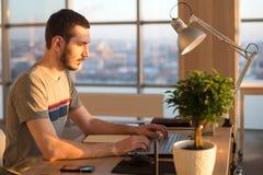 Geschäftsmann, der an Laptop am Schreibtisch im Büro arbeitet Stockfotografie