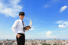 Geschäftsmann, der Laptop und Blick zu Ihnen verwendet Stockbilder