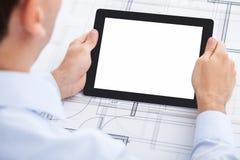 Geschäftsmann, der leere digitale Tablette über Blau hält Stockfotos