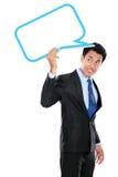 Geschäftsmann, der leere Textblase obenliegend hält Stockfoto