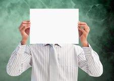 Geschäftsmann, der leeres Plakat vor seinem Gesicht gegen grünen Hintergrund hält Stockfotos