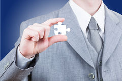 Geschäftsmann, der leeres Puzzlestück zeigt Stockfoto