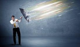 Geschäftsmann, der Lichtstrahlen mit Regenschirmkonzept verteidigt stockbild