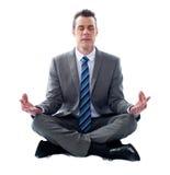 Geschäftsmann, der in Lotosstellung meditiert Stockbilder